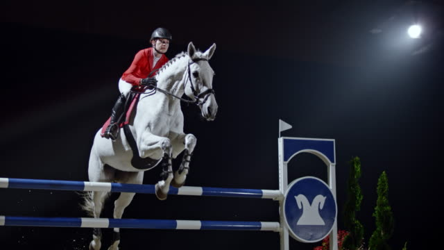 SLO MO Female rider on her white horse jumping a rail