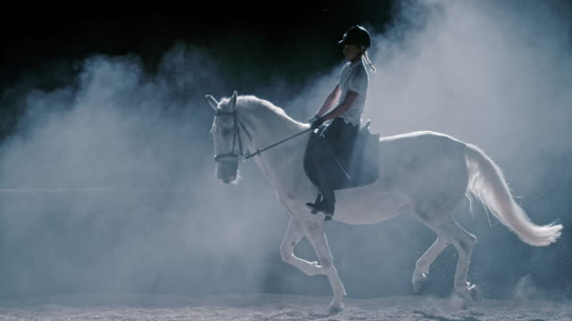 SLO MO LD Female riding a white horse at night
