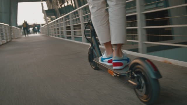 female riding electric push scooter on footbridge - motorino video stock e b–roll
