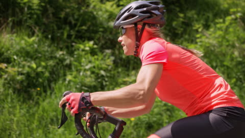 slo mo ts female road cyclist cycling up the road in sunshine - effort stock videos & royalty-free footage