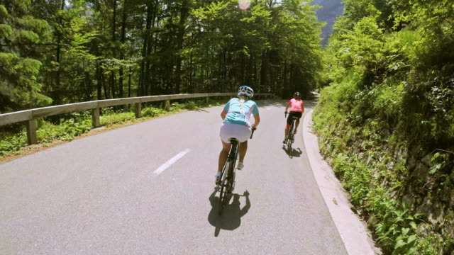 pov female road cyclist descending on a road down the mountain - bicycle trail outdoor sports stock videos & royalty-free footage