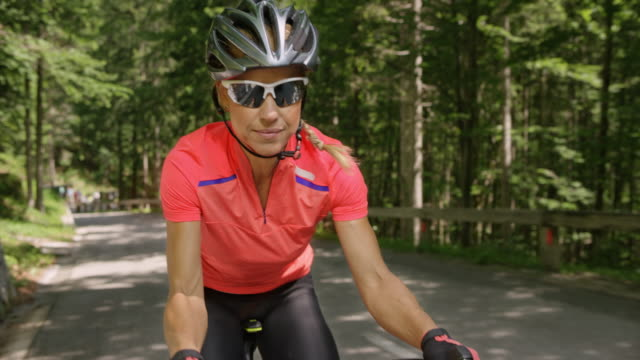 female road cyclist riding her bike on a nice mountain road in sunshine - cycling helmet stock videos & royalty-free footage