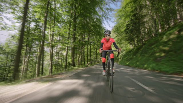 female road cyclist riding on a beautiful mountain road in sunshine - riding stock videos & royalty-free footage