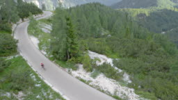 AERIAL Female road cyclist riding on a mountain road surrounded by forest