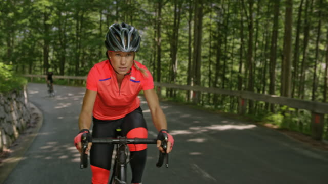 female road cyclist speeding up the mountain road leaving another cyclist behind - cycling helmet stock videos & royalty-free footage