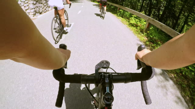 pov female road cyclists riding their bikes down a nice mountain road - passo montano video stock e b–roll