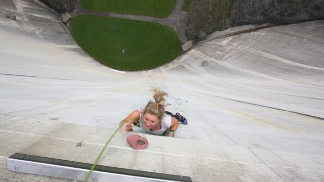 Female rock climber ascends artificial holds on concrete dam