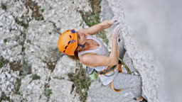 Female rock climber climbing up the cliff with a helmet on her head