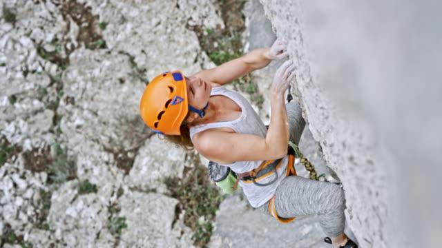 vídeos de stock, filmes e b-roll de feminino de alpinista escalando o penhasco com um capacete na cabeça dela - escalar