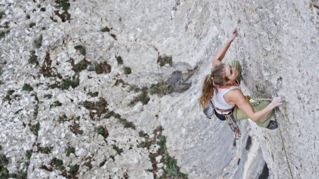slo mo female rock climber letting go while high in the rock wall - imbracatura di sicurezza video stock e b–roll