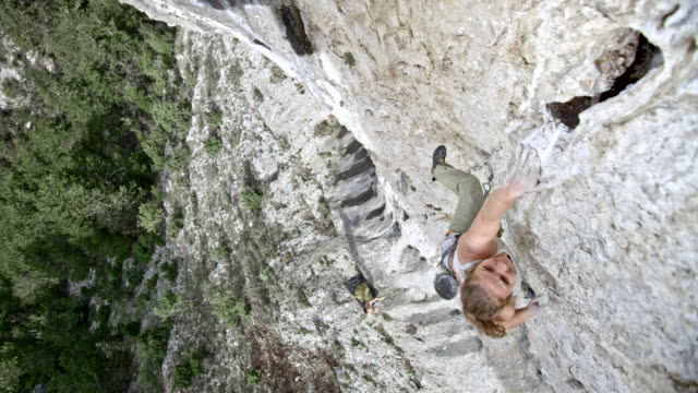vídeos de stock e filmes b-roll de slo mo female rock climber letting herself go while failing to get a grip in the cliff - equipamento de alpinismo