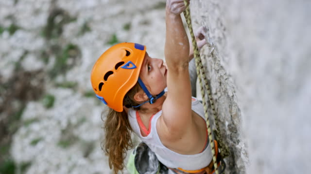 female rock climber securing herself as she climbs up the cliff - passione video stock e b–roll