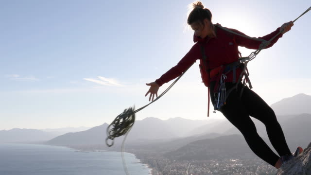 female rock climber tosses rope for rappel while leaning over cliff - protezione video stock e b–roll