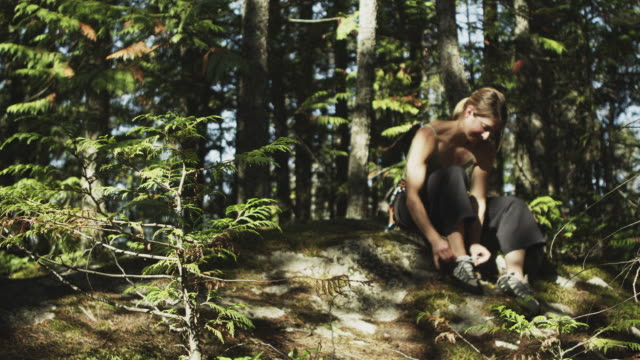 ms female rock climber tying shoe laces sitting on ground in forest, squamish, british columbia, canada - sitting on ground stock videos & royalty-free footage