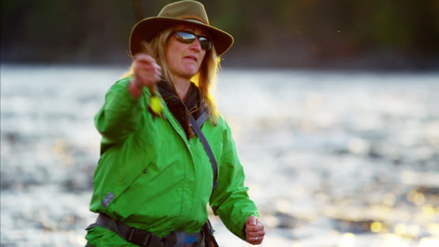 female rod and reel casting in river canada - fishing reel stock videos and b-roll footage