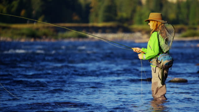 Female rod and reel casting in river Canada