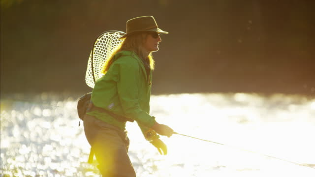stockvideo's en b-roll-footage met female rod and reel casting in river canada - hengel uitwerpen