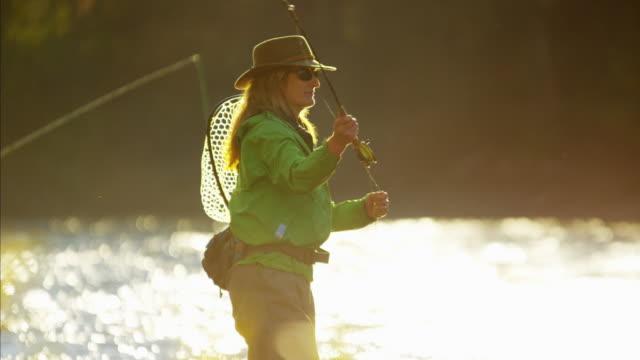 vidéos et rushes de female rod and reel casting in river canada - lancer la ligne de canne à pêche