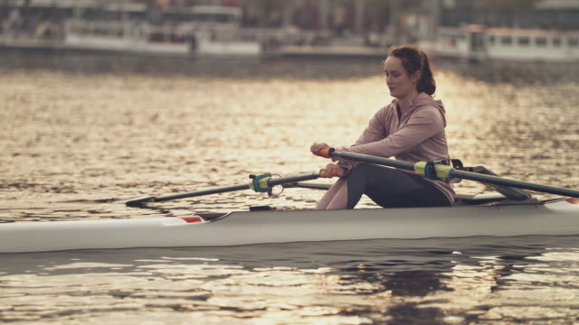 female rowing boat in city during sunset - rowing stock videos & royalty-free footage