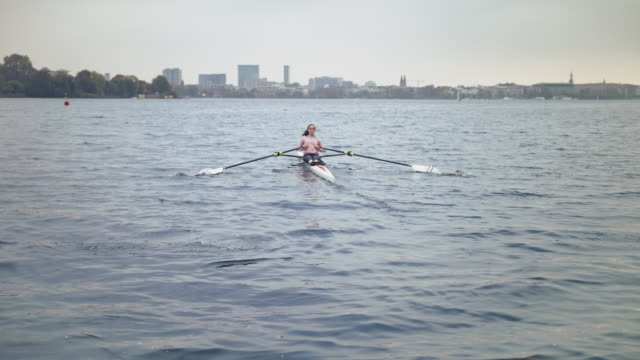 female rowing boat in river against sky - sculling stock videos & royalty-free footage