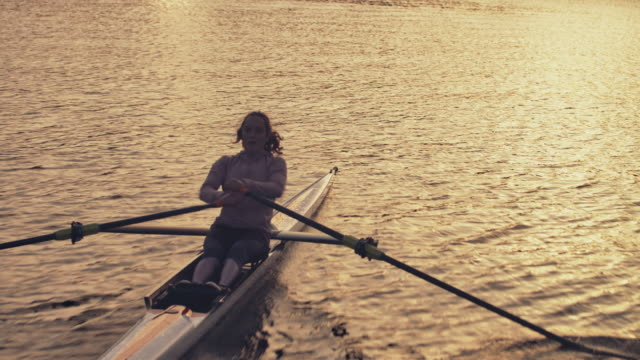 female rowing boat in river at sunset - rowing stock videos & royalty-free footage