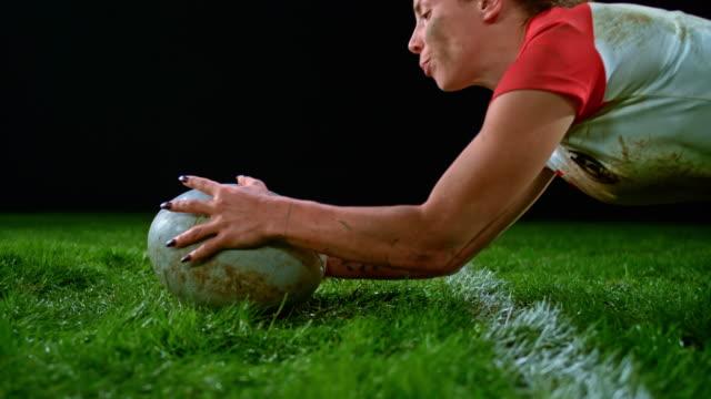slo mo 女子ラグビー選手がボールを持って地面に落ちてポイントを獲得 - スポーツ ラグビー点の映像素材/bロール