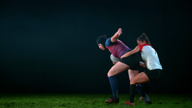 slo mo ld female rugby player holding her opponent by the waist and trying to stop her - rugby stock videos & royalty-free footage
