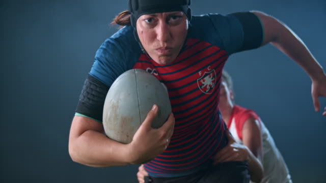 slo mo female rugby player holding the ball and outrunning her opponent - headwear stock videos & royalty-free footage