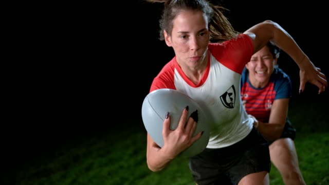 vídeos de stock e filmes b-roll de slo mo female rugby player holding the ball and running away from her opponent - studio shot
