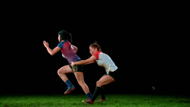 slo mo ld female rugby player trying to run away from her opponent holding her by the waist - rugby stock videos & royalty-free footage