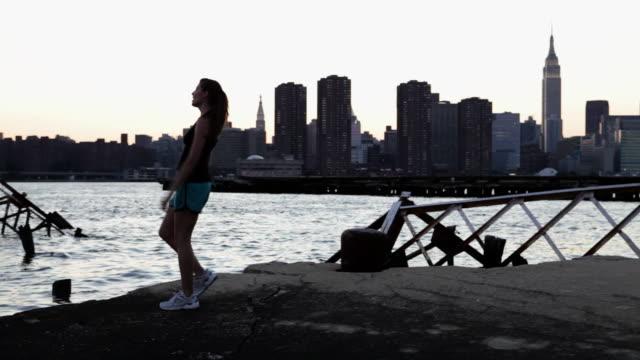 stockvideo's en b-roll-footage met female runner by river in brooklyn - gymbroek