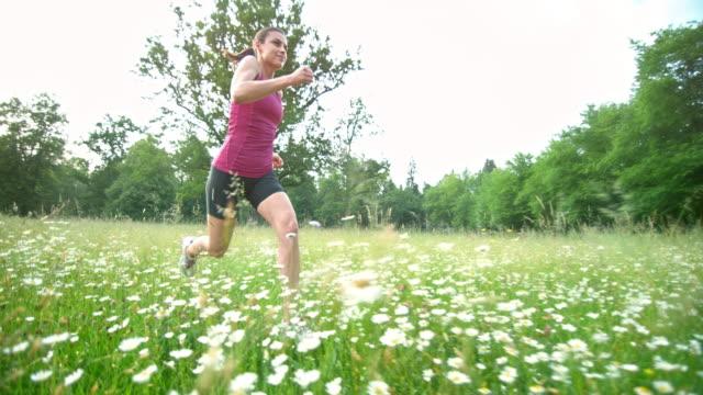 SLO MO TS Female runner going in high grass