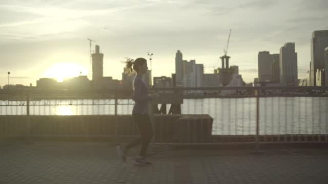 Female runner jogging by river Thames, London