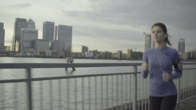 female runner jogging by river thames, london - 後ろで束ねた髪点の映像素材/bロール