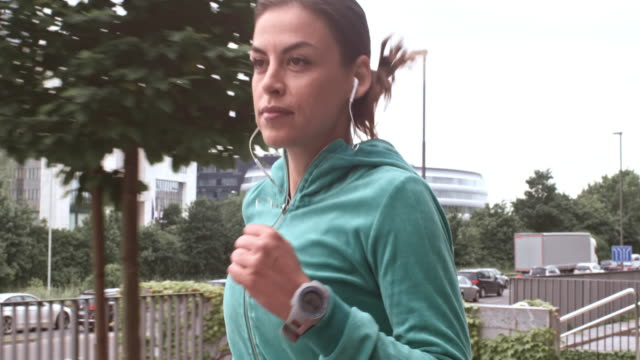 SLO MO TS Female runner listening to music