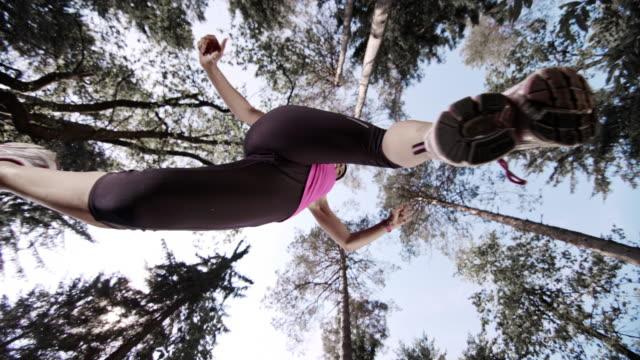 SLO MO Female runner making a jump below the tree tops
