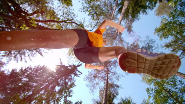 slo mo female runner making a jump in the forest - low angle view stock videos & royalty-free footage