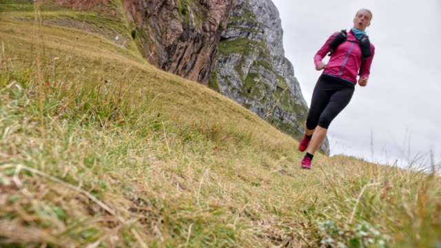 ld female runner running across a mountain meadow - pedal pushers stock videos & royalty-free footage