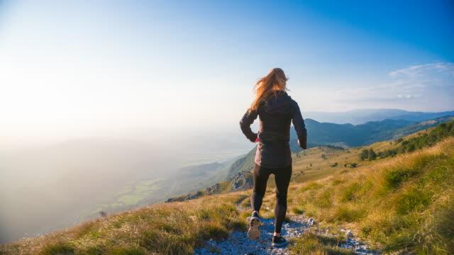 vidéos et rushes de coureur féminin dévalant une montagne, vue arrière - endurance