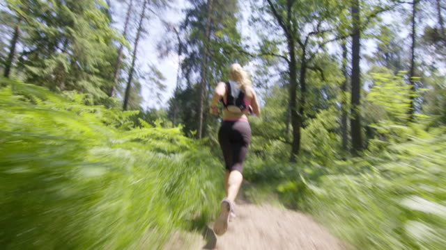 TS Female runner running down the forest path