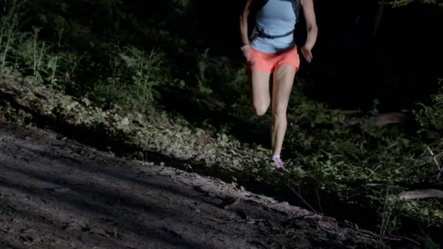 SLO MO Female runner running in forest at night