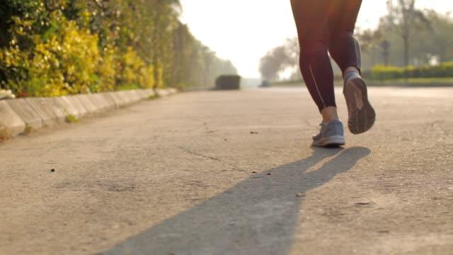 stockvideo's en b-roll-footage met slow motion: vrouwelijke atleet actief in het park, been close-up - jogster