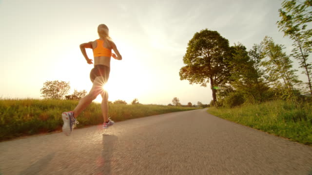 SLO MO TS Female runner running into sunset in countryside