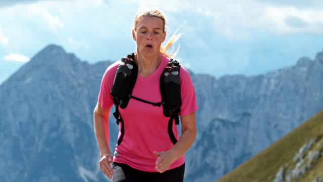 slo mo female runner running on a mountain trail in sunshine - day stock videos & royalty-free footage