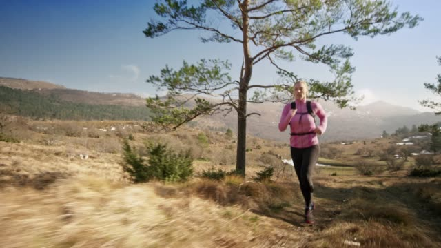 Female runner running on a mountain trail on a sunny day in early spring