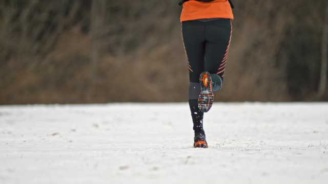 slo mo female runner running on a snow covered path - athlete stock videos & royalty-free footage