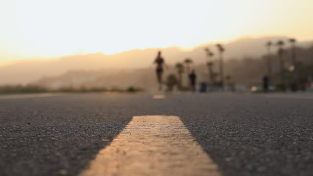 CU R/F Female runner running on bike path at sunset / Los Angeles, California, United States