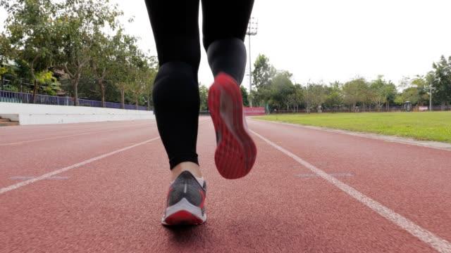 スローモーション: 女性ランナーのランニング トラック、脚で実行されているクローズ アップ - 陸上選手点の映像素材/bロール