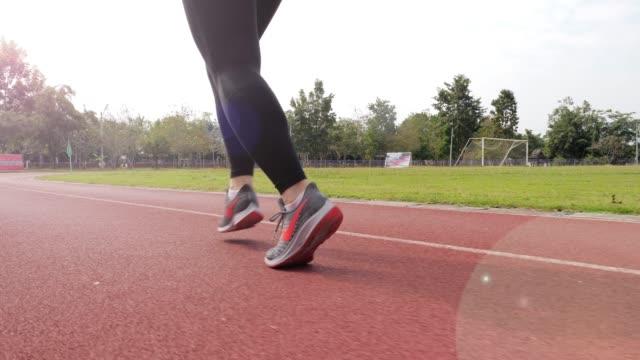 slow motion: female runner running on running track , leg close up - human limb stock videos & royalty-free footage