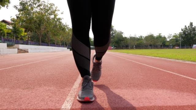 SLOW MOTION: Weiblicher Läufer auf Laufstrecke, Beinhaut-Nahaufnahme